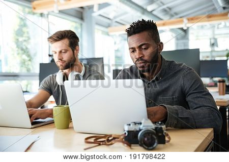 Image of serious young colleagues sitting in office coworking using laptop computers. Looking aside.