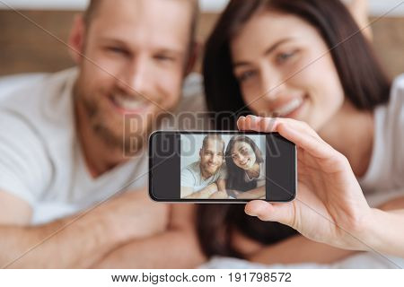 Morning selfie. Millennial man and woman grinning broadly while taking a selfie during an afternoon nap in bed.