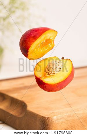Close up of a sliced whole nectarine flying above a wooden chopping board with vase of flowers