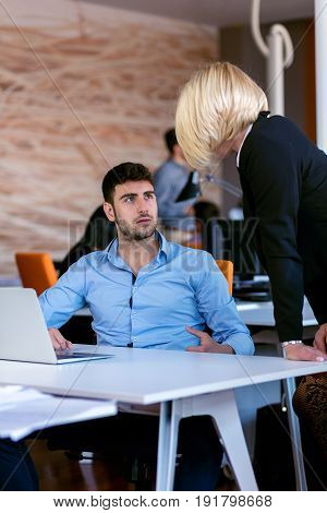 Boss scolding a shameful employee at work in an office.
