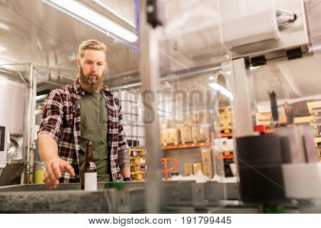 alcohol production, small business and people concept - man with bottle at craft beer brewery