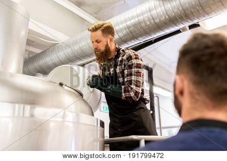 manufacture, business and people concept - men working at craft brewery or beer plant