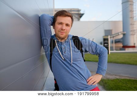 Caucasian handsome man in casual clothes with a friendly smile leaning against wall with a rough texture outdoors