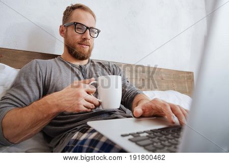 Working from home. Young man wearing pajamas enjoying the working process while holding a cup of coffee and looking on a laptop screen in bed.