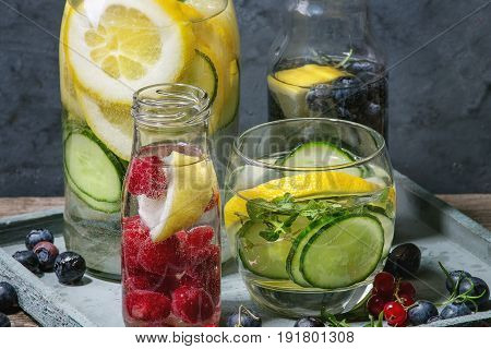 Citrus cucumber berries blueberry and raspberry sassy sassi water for detox in glass bottles on wooden blue background. Clean eating, healthy lifestyle concept, sunlight