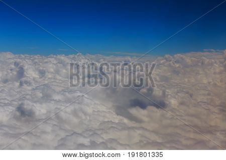 View From Above The Clouds With An Airplane Passing By