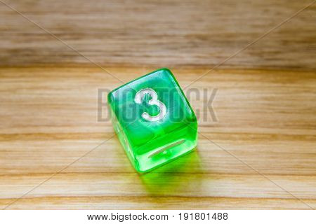 A Translucent Green Six Sided Playing Dice On A Wooden Background With Number Three On A Top