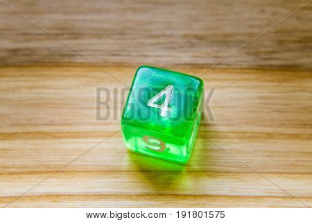 A Translucent Green Six Sided Playing Dice On A Wooden Background With Number Four On A Top