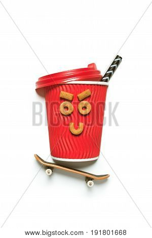 Close-up View Of Red Disposable Coffee Cup With Funny Face Made From Cookies And Small Skateboard Is