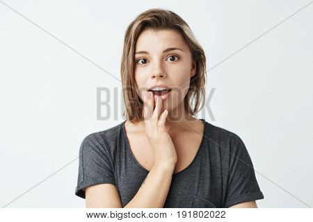 Surprised young beautiful girl smiling looking at camera over white background. Copy space.