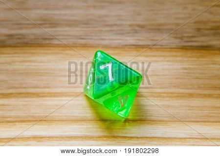 A Translucent Green Eight Sided Playing Dice On A Wooden Background With Number Seven On A Top