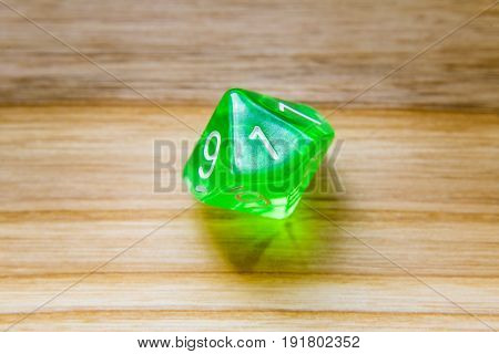 A Translucent Green Ten Sided Playing Dice On A Wooden Background With Number One On A Top
