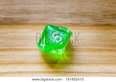 A Translucent Green Ten Sided Playing Dice On A Wooden Background With Number Six On A Top
