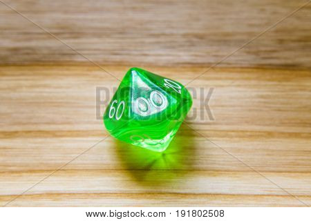 A Translucent Green Ten Sided Playing Dice On A Wooden Background With Two Zeros On A Top