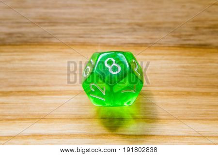A Translucent Green Twelve Sided Playing Dice On A Wooden Background With Number Eight On A Top