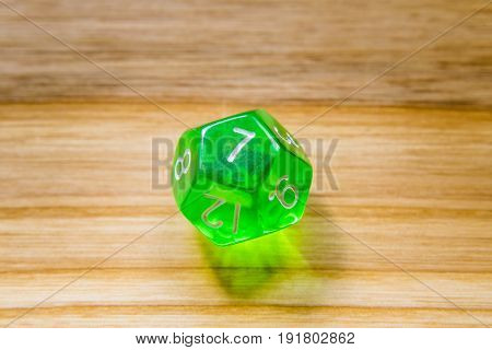 A Translucent Green Twelve Sided Playing Dice On A Wooden Background With Number Seven On A Top