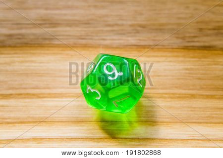 A Translucent Green Twelve Sided Playing Dice On A Wooden Background With Number Nine On A Top