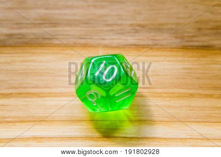 A Translucent Green Twelve Sided Playing Dice On A Wooden Background With Number Ten On A Top