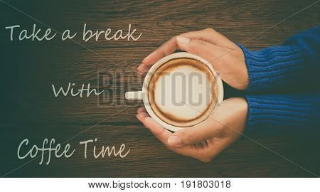 Young woman hand holding cup of mocca coffee on wooden table background