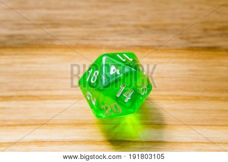 A Translucent Green Twenty Sided Playing Dice On A Wooden Background With Number Four On A Top