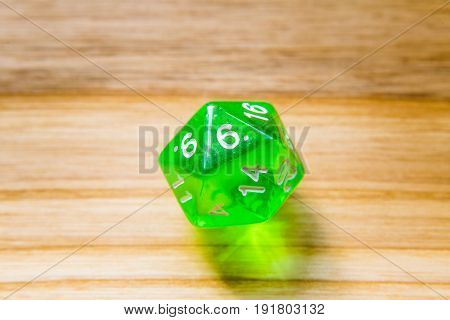 A Translucent Green Twenty Sided Playing Dice On A Wooden Background With Number Six On A Top