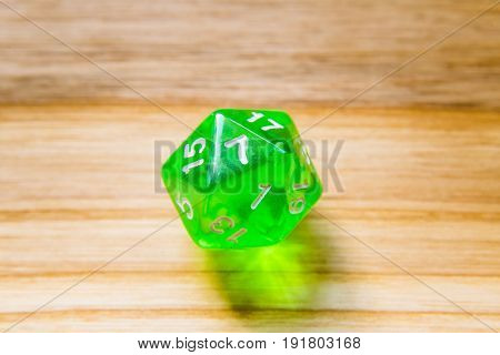 A Translucent Green Twenty Sided Playing Dice On A Wooden Background With Number Seven On A Top