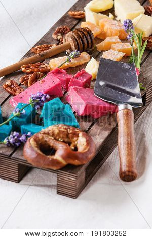 Variety of colorful holland cheese traditional soft, old, pink basil, blue lavender served with pecan nuts, honey, lavender flowers, pretzels bread on wood pallet over white linen background.