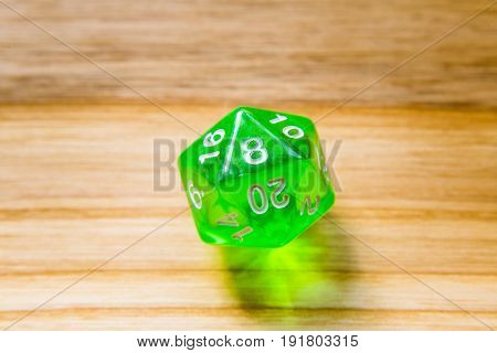 A Translucent Green Twenty Sided Playing Dice On A Wooden Background With Number Eight On A Top