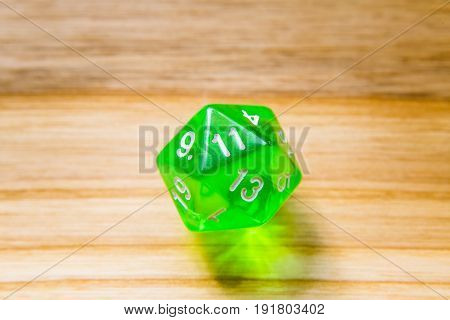 A Translucent Green Twenty Sided Playing Dice On A Wooden Background With Number Eleven On A Top