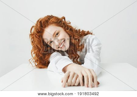 Happy pretty young girl with foxy curly hair smiling looking at camera laughing sitting at table over white background.