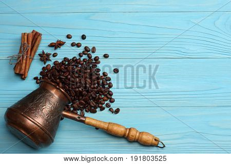 Coffee background. Vintage copper turkish coffee pot (cezve or ibrik), roasted coffee beans on blue wooden background. Top view with copy space.