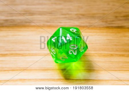A Translucent Green Twenty Sided Playing Dice On A Wooden Background With Number Fourteen On A Top