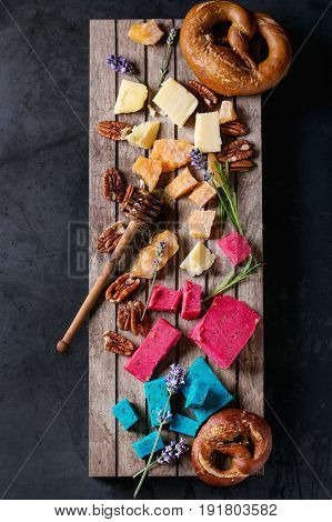 Variety of colorful holland cheese traditional soft, old, pink basil, blue lavender served with pecan nuts, honey, lavender flowers, pretzels bread on wood pallet over black metal background. Flat lay