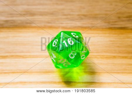 A Translucent Green Twenty Sided Playing Dice On A Wooden Background With Number Sixteen On A Top
