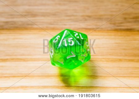 A Translucent Green Twenty Sided Playing Dice On A Wooden Background With Number Fifteen On A Top