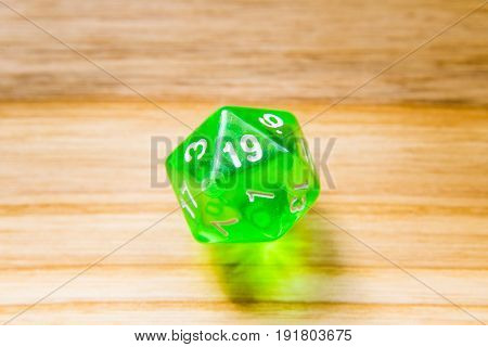 A Translucent Green Twenty Sided Playing Dice On A Wooden Background With Number Nineteen On A Top