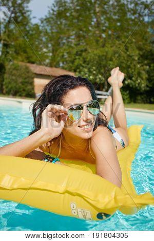 Young pretty fashion woman body posing in summer in pool with clear water lying on mattress in blue bikini and having fun