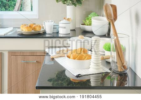 Bun, Bread And White Ceramic Dishware On Black Counter Top In The Kitchen
