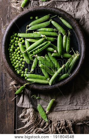 Young organic green pea pods and peas in terracotta tray over old dark wooden planks with sackcloth textile background. Top view with space. Harvest, healthy eating.