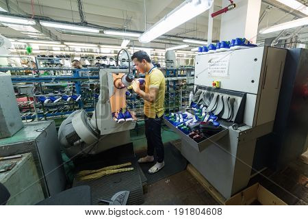 MOSCOW, RUSSIA - FEBRUARY 21, 2017: Moscow shoe factory JSC RALF RINGER. Worker working in a shoe factory, finishing at a grinder machine