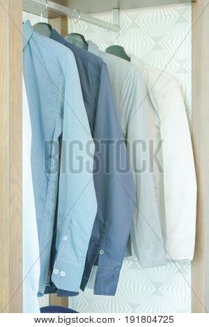 Shirts And Men's Suit Hanging In Closet