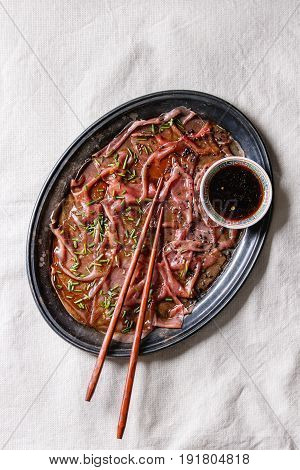 Asian style Beef carpaccio with soy sauce, chive onion, black sesame, served on vintage metal tray with bowl of sauce and chopsticks over white textile linen background. Top view with space