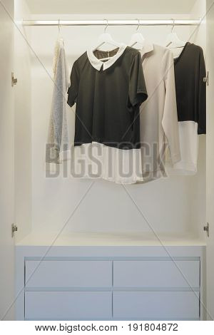 Black And White Blouses Hanging In White Wardrobe