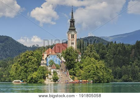 Bled, Slovenia - June 3, 2017: Close Up Of The Church In The Center Of Bled Lake With Several Touris