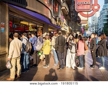Shanghai, China - Nov 4, 2016: On Nanjing Road Pedestrian Street - A queue outside a food store in late afternoon sunlight. Street photography.