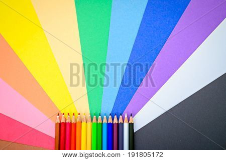 Close up macro shot of sharp colorful pencils on colorful paper background