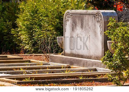 The marble tombstone and several graves in the row closeup on the Oakland Cemetery in sunny day Atlanta USA