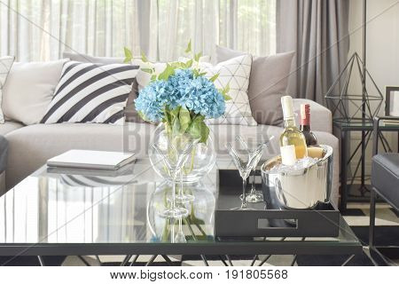 Light Blue Flower With Wine Bottles And Glasses Of Wine On The Tabla In Modern Living Room
