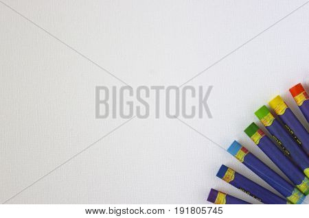 Rainbow colored oil pastels in fan  on white background