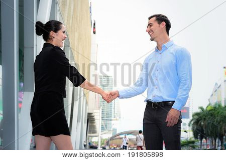 businessman and businesswoman shaking hands smile for success agreement at the outdoor place